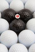 White and black golf balls and wooden tee — Stock Photo