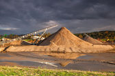 Quarry sand on a bank of a river — Stock Photo