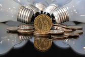 Wasteful bulbs and U.S. dollar coins — Stock Photo