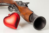 Old gun and red heart — Stock fotografie