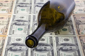 Empty wine bottle and US dollars — Stock Photo