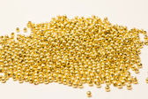 Gold beads on white — Stock Photo
