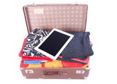 Vintage leather suitcase overstuffed with Tablet gadget — Stock Photo