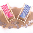 1 and 2 euro coins lie in front of toy beach chairs — 图库照片