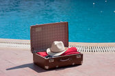 Vintage suitcase near the pool — Stock Photo