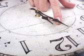 Female finger changes the time on a clock — Stock fotografie