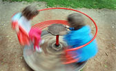 Red children carousel spinning round — Stock Photo