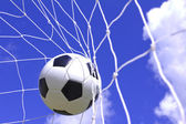Soccer ball in net on blue sky — Stock Photo