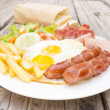American breakfast with fried eggs, bacon, sausages, toasts and — Stock Photo