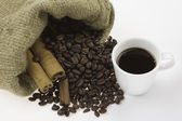 A cup of coffee, and cinnamon, coffee beans — Stock Photo
