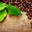 Coffee on wooden background with green leaves - Stock Photo