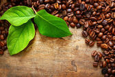 Coffee on wooden background with green leaves — Stok fotoğraf