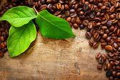 Kaffe på trä bakgrund med gröna blad — Stockfoto
