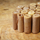Waffle rolls standing on wooden background — Stock Photo