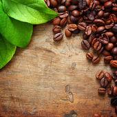 кофе на деревянных фон с зелеными листьями — Стоковое фото