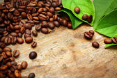Coffee on wooden background with green leaves — Stock Photo