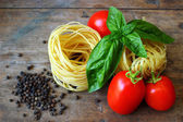Raw tagliatelle with tomatoes on wooden background — Stock Photo