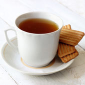 Cup of tea with cookies on white painted wooden background — ストック写真