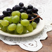 Grapes on white plate — Stock Photo