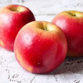 Red apples on weaved tablecloth — Stock Photo