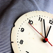 Klocka på randigt tyg — Stockfoto