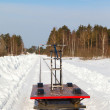 Handcar on a narrow track in snow and blue sky — Stock Photo