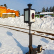 Old railway arrow with a lantern in snow - Stock Photo