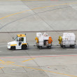 Stock Photo: Tug and luggage on airport tarmac