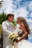 Wedding bouquet and newlyweds — Stock Photo