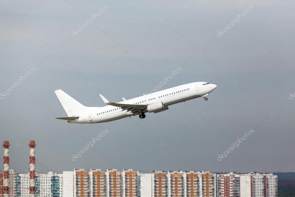 白色飞机从房子的背景上跑道起飞