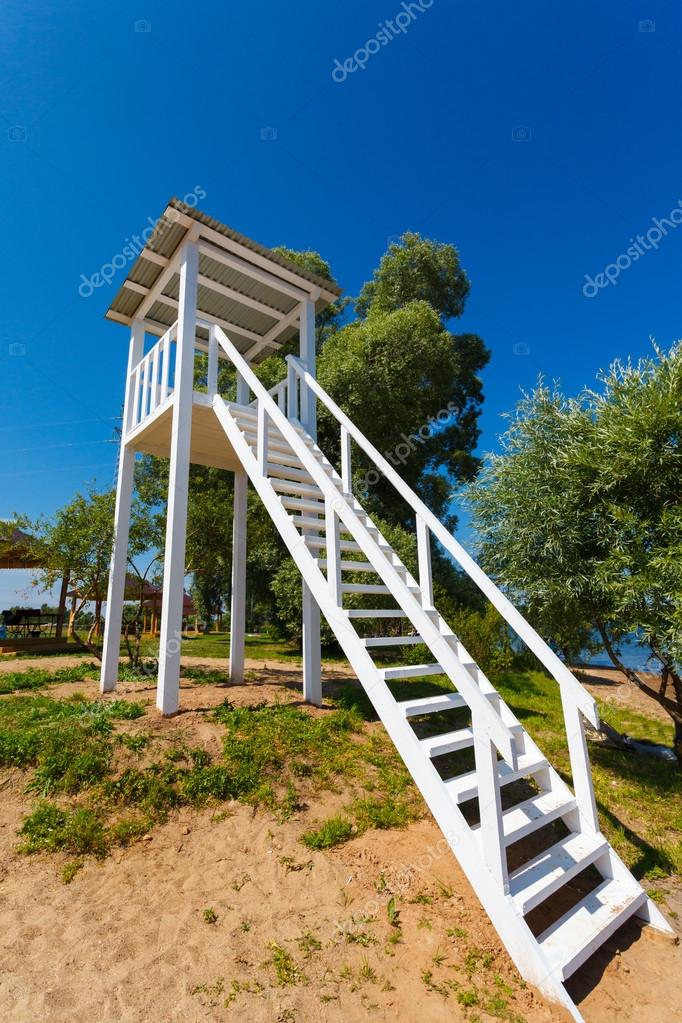 白色的瞭望塔在一处海滩上背景蓝色天空– 图库图片