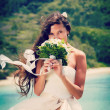 Bride, beautiful young girl with dark hair in white wedding dress with bouquet on background of beach with blue water, Seychelles — Stock Photo #51300021
