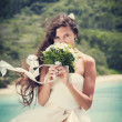 Bride, beautiful young girl with dark hair in white wedding dress with bouquet on background of beach with blue water, Seychelles — Stock Photo #51300027