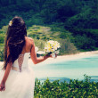 Bride, beautiful young girl with dark hair in white wedding dress with  bouquet on  background of beach with blue water, Seychelles — Stock Photo #51300035