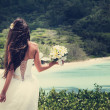 Bride, beautiful young girl with dark hair in white wedding dress with  bouquet on  background of beach with blue water, Seychelles — Stock Photo #51300039