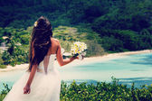 Bride, beautiful young girl with dark hair in white wedding dress with  bouquet on  background of beach with blue water, Seychelles — Stock Photo