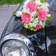 Stock Photo: Bridal bouquet lying on black car