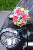 Bridal bouquet lying on a black car — Stock Photo