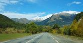 Empty road toward mountains inside Switzerland — Stock Photo