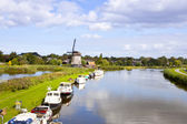 Dutch wind mill at river with little boats — Stock Photo