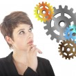 Stock Photo: Young woman thinking with gears isolated on white background