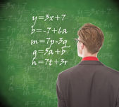 Young student looking at chalkboard with mathematics — Stock Photo