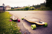 Longboard by the asphalt road at the border of a village. Toned image. — Stock Photo