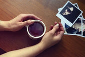 Hands holding a cup with tea and photos — Stock Photo