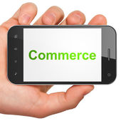 Hand holding smartphone with word Commerce on display. Generic m — Stock Photo