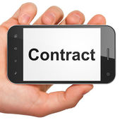 Hand holding smartphone with word Contract on display. Generic m — Stock Photo