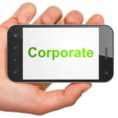 Hand holding smartphone with word Corporate on display. Generic — Stock Photo