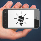 Finance concept: smartphone with Energy Saving Lamp. — Stok fotoğraf