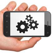 Information concept: Gears on smartphone — Stockfoto