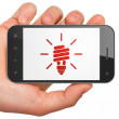 Finance concept: Energy Saving Lamp on smartphone — Stock Photo